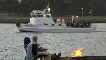 sportfishing: SAN DIEGO, CALIFORNIA, JUNE 23. Mission Bay on June 23, 2015, in San Diego, California. A senior couple watches the Sea Watch cruise by from their beach campfire on Mission Bay in San Diego in California. Editorial
