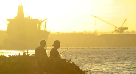 superstructure: A Sunset Over Ship Superstructures of Naval Base Coronado in San Diego Provides the Backdrop as Two Men Fish in the Foreground Stock Photo