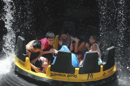 drench: SAN DIEGO, CALIFORNIA, JUNE 25. SeaWorld on June 25, 2015, in San Diego, California. Visitors ride the thrilling Shipwreck Rapids at SeaWorld in San Diego in California.