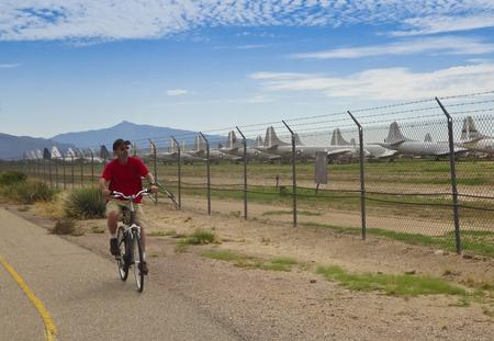 bikeway: TUCSON, ARIZONA, SEPTEMBER 7. The Aviation Bikeway on September 7, 2015, in Tucson, Arizona. A cyclist views the Davis Monthan Air Base Boneyard on the Aviation Bikeway, a 9.1 mile bike trail in Tucson, Arizona.