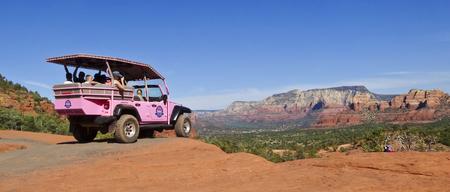 wheeling: SEDONA, ARIZONA, OCTOBER 15. Broken Arrow Trail on October 15, 2015, near Sedona, Arizona. A photographer shoots a Pink Jeep Tours vehicle loaded with tourists on the Broken Arrow Trail near Sedona.