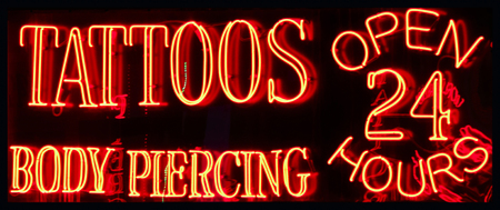 shop sign: A Neon Sign Advertising a Tattoo and Body Piercing Parlor Open 24 Hours