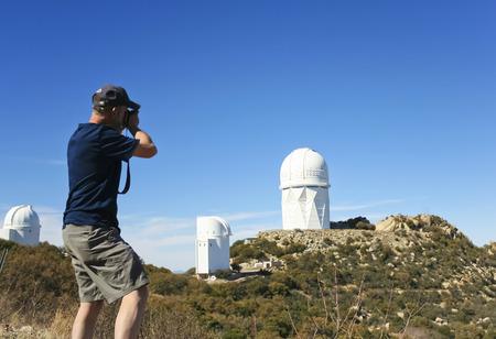 tucson: TUCSON, ARIZONA, FEBRUARY 28. Kitt Peak National Observatory on February 28, 2016, near Tucson, Arizona.  A man photographs the Mayall 4m Telescope at Kitt Peak National Observatory. Editorial
