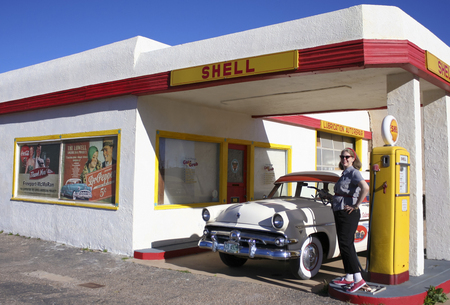 refurbished: BISBEE, ARIZONA, FEBRUARY 25: The historic Lowell district on February 25, 2016, in Bisbee, Arizona. A model dressed 50s style poses by a refurbished 50s Ford Station Wagon and Shell gas pumps in historic Lowell, Arizona. Editorial
