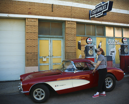 refurbished: BISBEE, ARIZONA, FEBRUARY 25: The historic Lowell district on February 25, 2016, in Bisbee, Arizona. A model dressed 50s style poses by a refurbished late 50s Chevrolet Corvette and Mobilgas pumps in historic Lowell, Arizona. Editorial