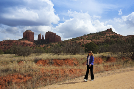 coconino national forest: A Woman Walks Along a Dirt Road Near Sedonas Famous Cathedral Rock Stock Photo