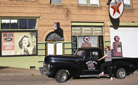 refurbished: BISBEE, ARIZONA, FEBRUARY 25: The historic Lowell district on February 25, 2016, in Bisbee, Arizona. A model dressed 50s style poses by a refurbished 50s Texaco gas station in historic Lowell, Arizona. Editorial