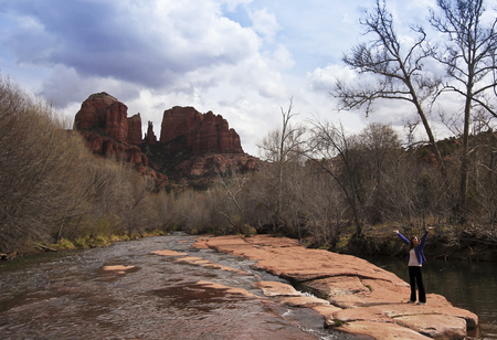 coconino national forest: A Joyous Woman Hikes Along Oak Creek Near Sedonas Famous Cathedral Rock