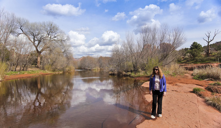 coconino national forest: A Woman Walks Along Oak Creek Near Sedonas Famous Cathedral Rock Stock Photo
