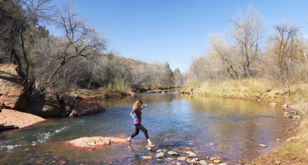A Woman Crosses a Creek by Leaping from Rock to Rock