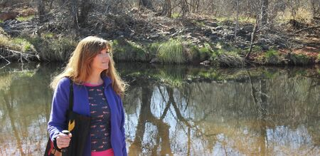 coconino national forest: A Woman Hikes Along a Creek in the Warm Sunshine