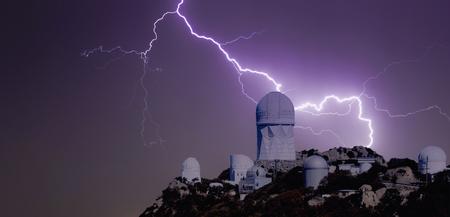 Un rayo huelgas por un Observatorio cima de la montaña en la noche