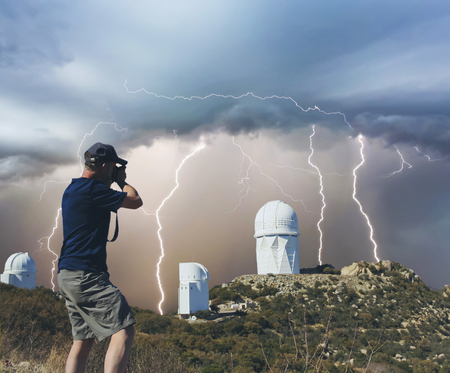 mountaintop: A Man Photographs Mountaintop Observatory Telescopes During a Monsoon Thunderstorm Stock Photo