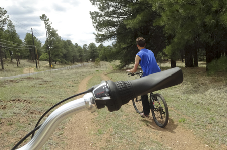 flagstaff: A handlebar gets in the shot of a young man on his hybrid bicycle while riding the Flagstaff Urban Trail System ( FUTS ) in Flagstaff, Arziona.