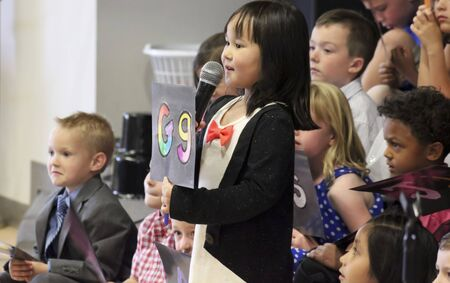 reciting: SUMMERLIN, NEVADA, MAY 26. Ethel W. Staton Elementary School on May 26, 2016, in Summerlin, Nevada. A little girl with a microphone holds up the letter G at a kindergarten graduation at Ethel W. Staton Elementary School in Summerlin, Nevada.