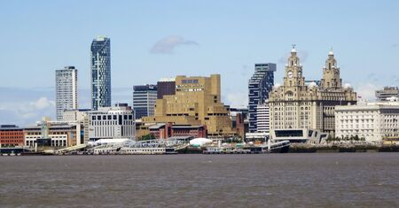 merseyside: LIVERPOOL, ENGLAND, JULY 3. Pier Head from across the Mersey River on July 3, 2016, in Liverpool, England. Liverpool landmarks include The Royal Liver Building, Merseyside, Cunard Building, Beetham Towers, Plaza, Unity Residential and New Hall Place. Editorial