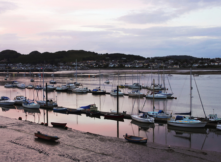 harbors: CONWY, WALES, JUNE 27: Conwy River on June 27, 2016, in Conwy, Wales. The River Conwy harbors a fleet of boats as the lights come on in Deganwy, Wales.