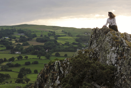 crag: A Beautiful Woman Gazes Down at the Valley Floor from Atop a Windy Crag in Wales Stock Photo