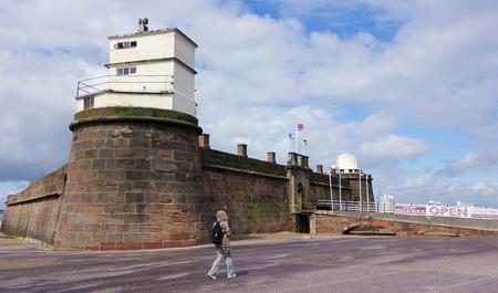 mersey: NEW BRIGHTON, ENGLAND, JUNE 29. Fort Perch Rock on June 29, 2016, in New Brighton, England. A woman walks near to Fort Perch Rock, New Brighton, Merseyside, England