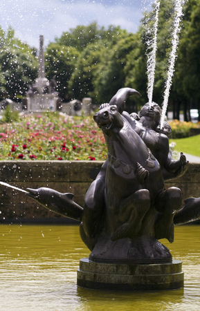 pink dolphin: PORT SUNLIGHT, ENGLAND, JUNE 29. A pool and fountain on June 29, 2016, in Port Sunlight, England. A man and boy on a horse flanked by dolphins sprays water into a pool in Port Sunlight, England. The War Memorial is in the background.