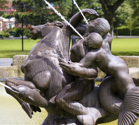 merman: PORT SUNLIGHT, ENGLAND, JUNE 29. A pool and fountain on June 29, 2016, in Port Sunlight, England. A man and boy on a horse flanked by dolphins sprays water into a pool in Port Sunlight, England.