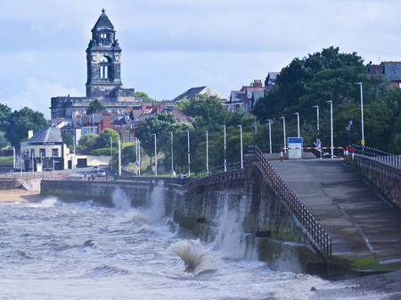 SEACOMBE, ENGLAND, JUNE 29. The Seacombe Promenade on June 29, 2016, in Seacombe, England. Waves crash along the Seacombe Promenade in Seacombe, England, as the Wallasey Town Hall looms in the background. 新聞圖片