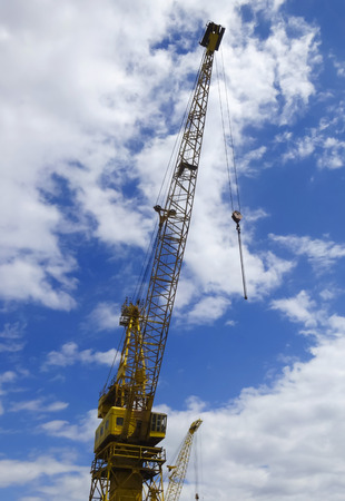 poleas: A Towering Yellow Crane Against a Blue Sky with White Clouds