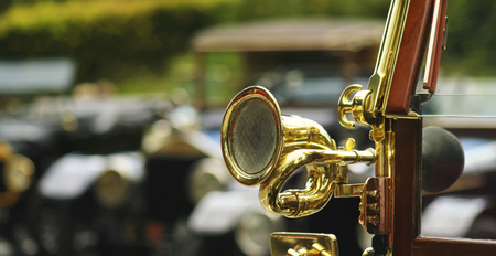 motor cars: An Antique Brass Car Horn on  the Windshield of a Vintage Automobile Stock Photo