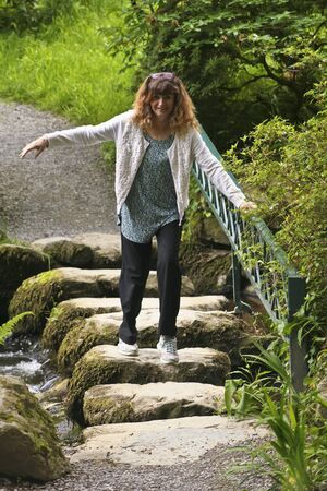 tentative: A Woman Holds a Railing as She Tentatively Crosses a Creek on Stepping Stones