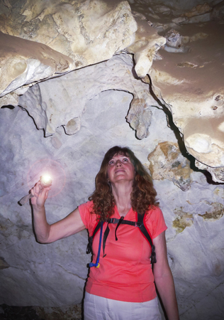 A Woman Deep in a Cave Examines Rock Formations with a Flashlight Banco de Imagens