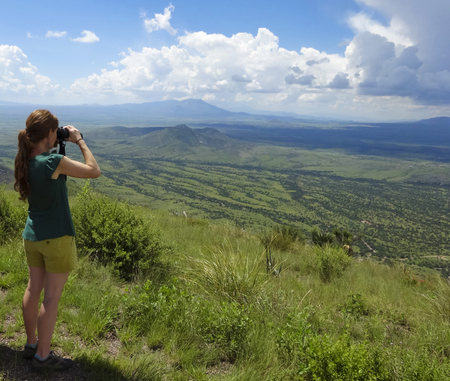 SIERRA VISTA, ARIZONA, AUGUST 21. Coronado Peak on August 21, 2016, near Sierra Vista, Arizona. A woman gazes into Mexico on top of Coronado Peak in the Huachuca Mountains near Sierra Vista, Arizona. Stock Photo