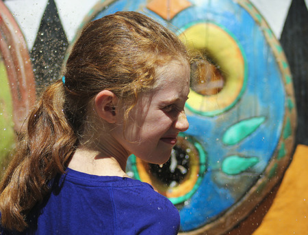 TUCSON, ARIZONA, AUGUST 27. Reid Park Zoo on August 27, 2016, in Tucson, Arizona. A red haired girl gets sprayed by an African mask at the Reid Park Zoo, one of Tucson, Arizona's biggest tourist draws.