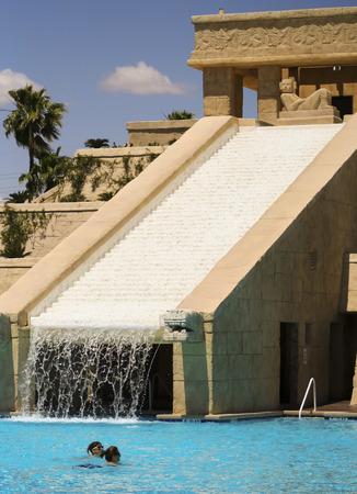 bathers: LAS VEGAS, NEVADA, MAY 23. The Cancun Resort on May 23, 2016, in Las Vegas, Nevada. A pair of bathers enjoys the dramatic Mayan waterscape and pyramid at the Cancun Resort in Las Vegas, Nevada.
