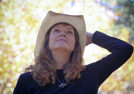 A Portrait of a Cowgirl with Autumn Leaves in the Background
