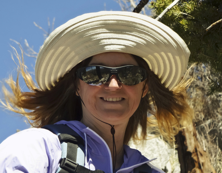gusty: A Smiling Woman Hiking with the Wind Blowing Her Hair Stock Photo