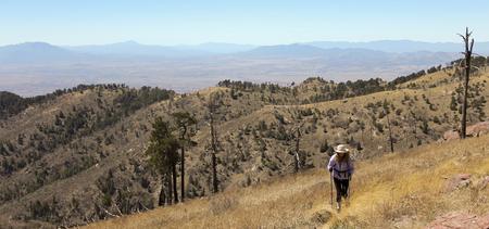 Une femme randonneuse fait son chemin vers le haut d'une pente de haute montagne Banque d'images - 76652354