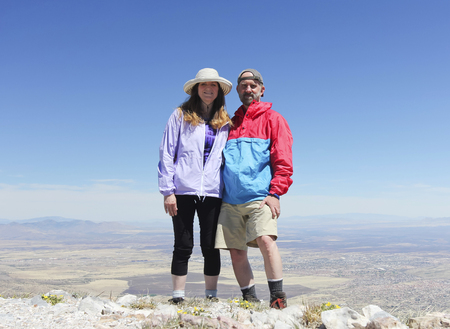 A Smiling Couple Poses on the Summit of a Mountain Peak