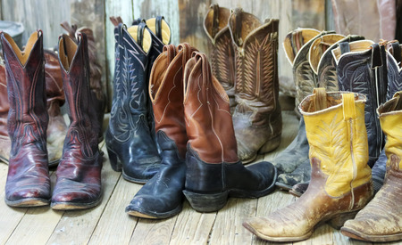 Een groepering van negen paren oude cowboy laarzen op een plank bunkhouse verdieping Stockfoto