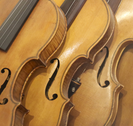bluegrass: A Leaning Stack of Vintage Antique Violins or Fiddles Stock Photo