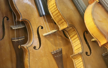 fiddles: A Leaning Stack of Vintage Antique Violins or Fiddles Stock Photo