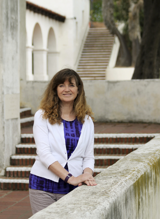 A Smiling Woman Stands Amid the Stairs and Arches of Spanish Revival Style Architecture