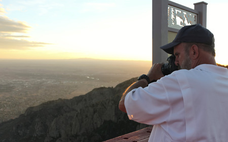 A Photographer Shoots Images on the Sandia Peak Aerial Tramway Observation Deck at Sunset Banco de Imagens