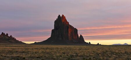 A Glowing Shiprock Landscape Against a Striated Sunrise Sky, New Mexico, on the Navajo Reservation, west of the town of Shiprock. Stock Photo