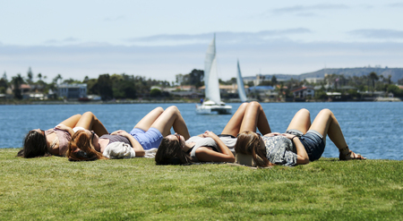 SAN DIEGO, CALIFORNIA, JUNE 9: Seaport Village on June 9, 2017, in San Diego, California. A Quartet of Young Woman Sunning Themselves at Embarcadero Park in Seaport Village in San Diego. Editorial