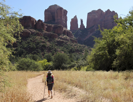 coconino national forest: A Woman Hikes the Baldwin Trail Toward Famous Cathedral Rock Near Sedona, Arizona