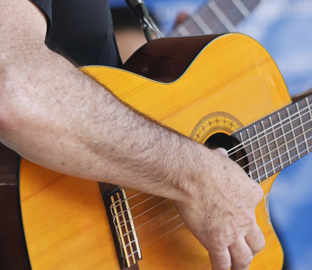 A Musician Plays a Classical Cutaway Guitar with Another Guitar in the Background