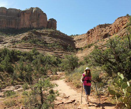 coconino national forest: A Woman Hikes the Templeton Trail Down from Famous Cathedral Rock Near Sedona, Arizona
