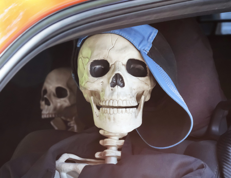 A Pair of Teen Skeletons in a Car Sitting in Traffic