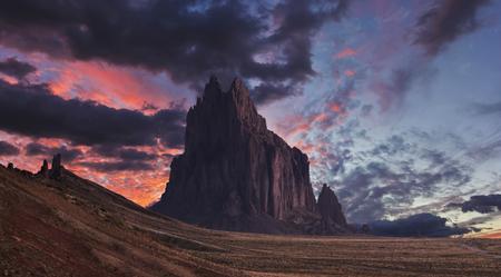 Een Shiprock-landschap tegen een adembenemende schemeringhemel, New Mexico, op het Navajo-reservaat, ten westen van de stad Shiprock. Stockfoto