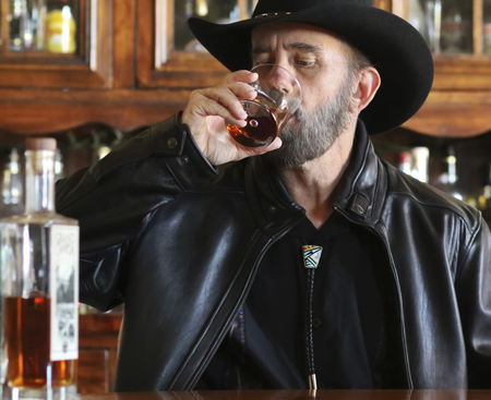 A Bearded Cowboy in Black Sitting Alone in a Saloon Drinking Whiskey Stock Photo